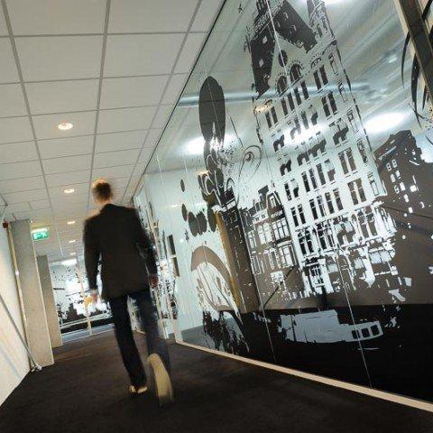 <strong>Transparante creatief bestickerde glazen wand in de gang bij ZAPP office Rotterdam</strong> Zo heb je toch de verbinding met andere bedrijven om je heen maar ook de zelfstandigheid en rust wanneer gewenst. Een informeel netwerk van ondernemers. Dat is prettig samenwerken in het kantoorgebouw. Zelfs de gang is mooi bij ZAPP office!